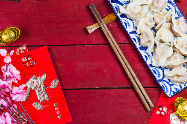 Chinese Jiaozi new year food, spring festival food on traditional spring festival Spring festival atmosphere and dumplings, ang pow or red packet and gold ingots. Chinese characters means luck,wealth